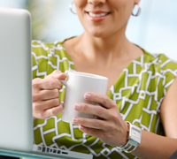 Woman working at laptop holding coffee mug.