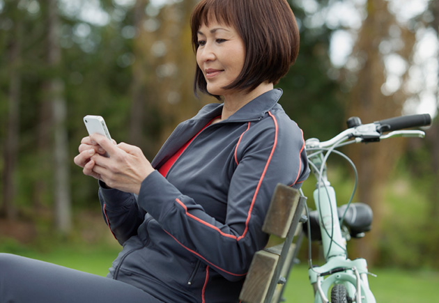 Woman using smartphone while relaxing on park bench.