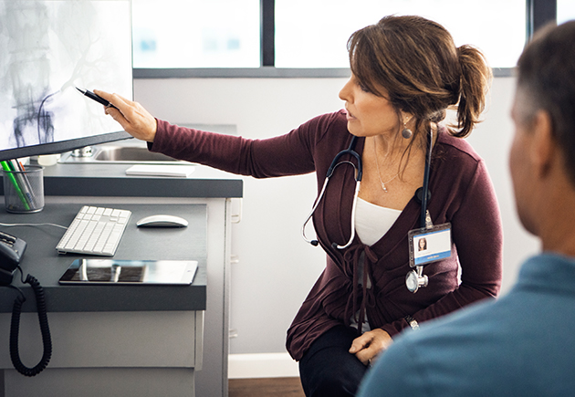 Doctor pointing to digital x-ray while speaking with patient.