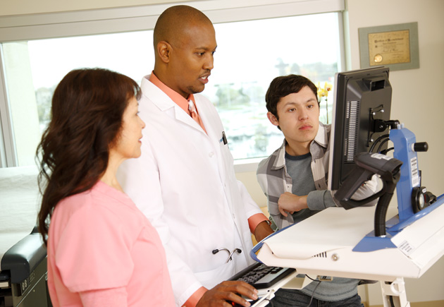 Doctor, nurse, and patient reviewing medical information together on computer.