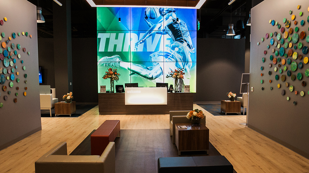 Large modern reception area with blond wood floors and large lit up artwork of an athlete jumping with the word Thrive behind the desk