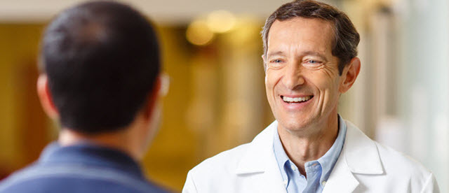 Doctor smiling and greeting patient in hospital hallway