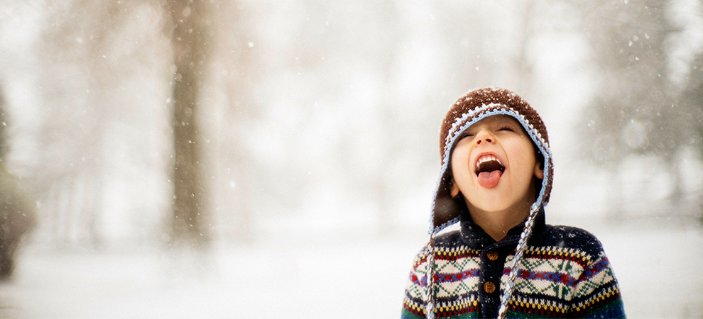 Little boy touching snowflakes with tongue