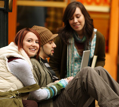 Three millennials looking at laptop outside in cold