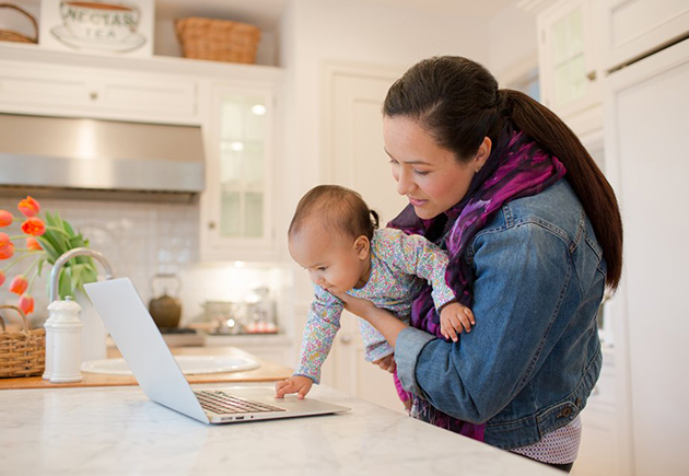 Woman looking at laptop while holding young child at home.