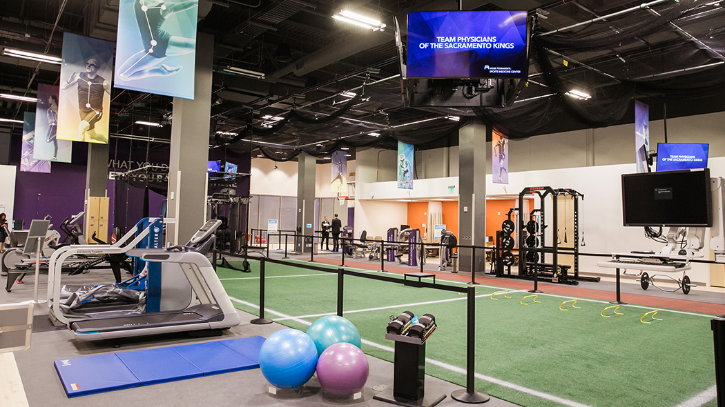 Rehabilitation open space and equipment room has images of athletes and TVs hanging from the ceiling; exercise machines, weights, mats and balls along the walls; and artificial turf running through the center