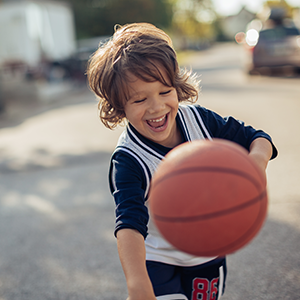 Child playing with a basketball outdoors.