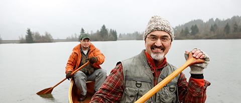 Older father and son canoeing on lake.