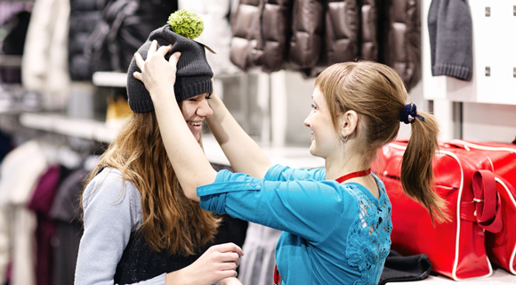 Two women in fitness store trying on a hat