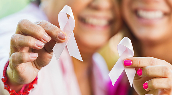 Two women holding up pink ribbons for breast cancer