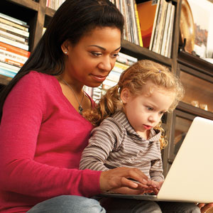 A woman and child sit facing a laptop.