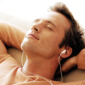 A man wearing earbuds relaxes.