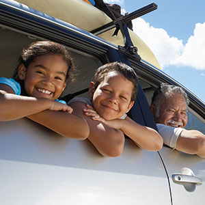 A man and two children smile out the windows of a car.