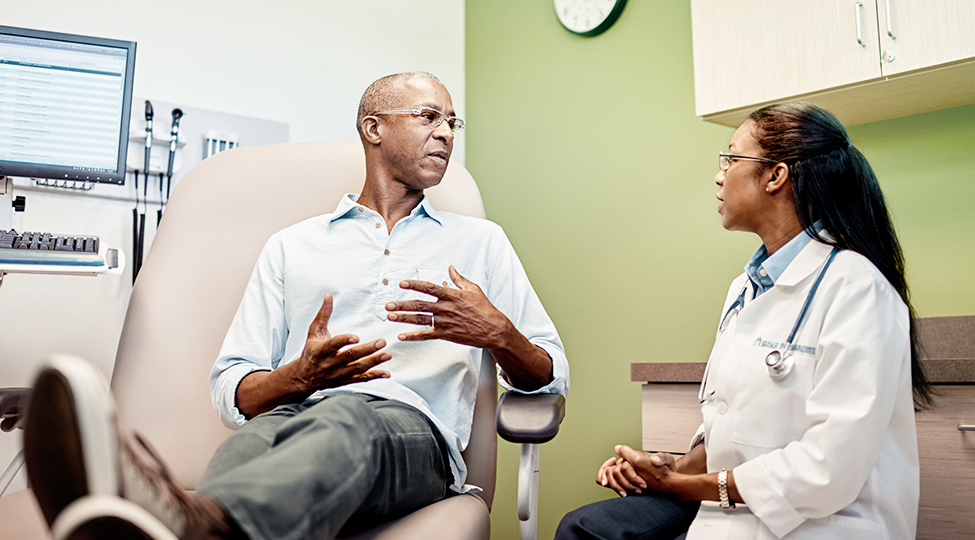 Patient discussing concerns with his doctor in medical office.
