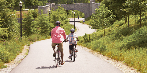Father and son riding bicycles along scenic bike path.