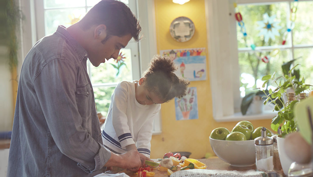 Girl helping dad chopping vegetables in kitchen