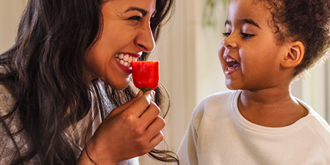 Mother demonstrating healthy eating with her child by eating a pepper.
