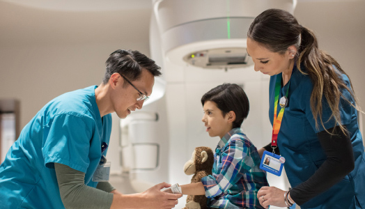Boy with stuffed animal treated by doctor and nurse