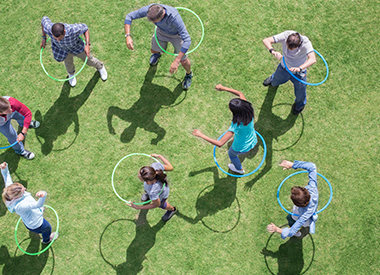 8 people playing hula hoop.