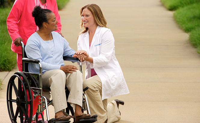 Medical professional kneeling to speak with woman in wheelchairs outdoors.