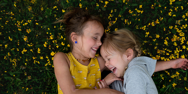 Two young girls laughing while lying on flower covered grass.