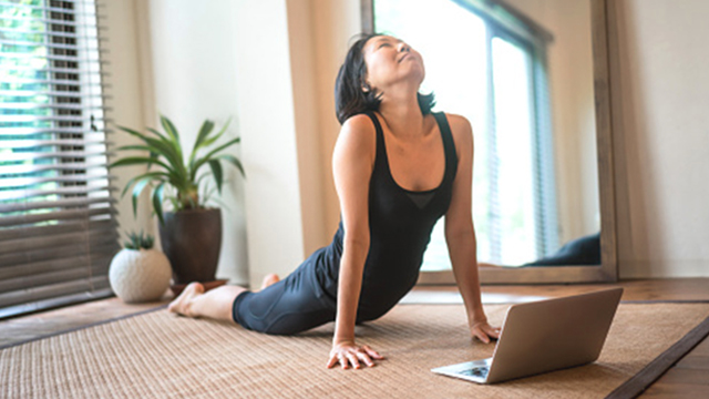 Woman in yoga cobra pose with help from info on laptop.