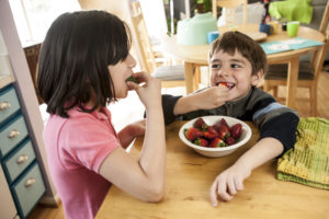 Hispanic children eating strawberries