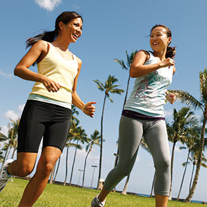 Two beaming women jog past palm trees.