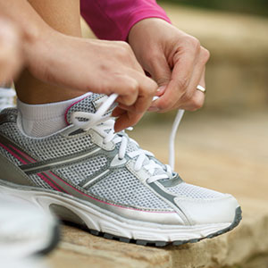 A pair of hands laces up a running shoe.