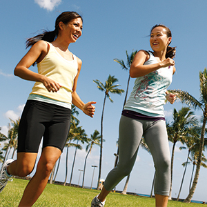 2 smiling women jog past palm trees.