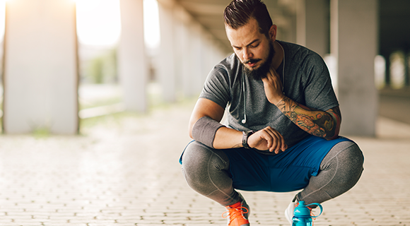 Man in workout gear crouching and taking pulse