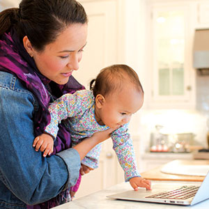 A woman shows a laptop to a baby in her arms.
