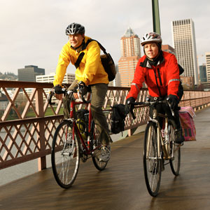 Two cyclists ride on an urban bridge.