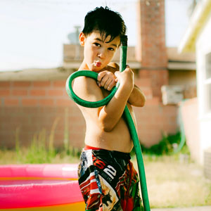 A little boy plays with a garden hose.