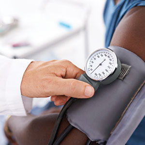 A blood pressure monitor cuff shows a reading on its dial.