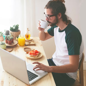 A man enjoys a healthy snack while using a laptop.