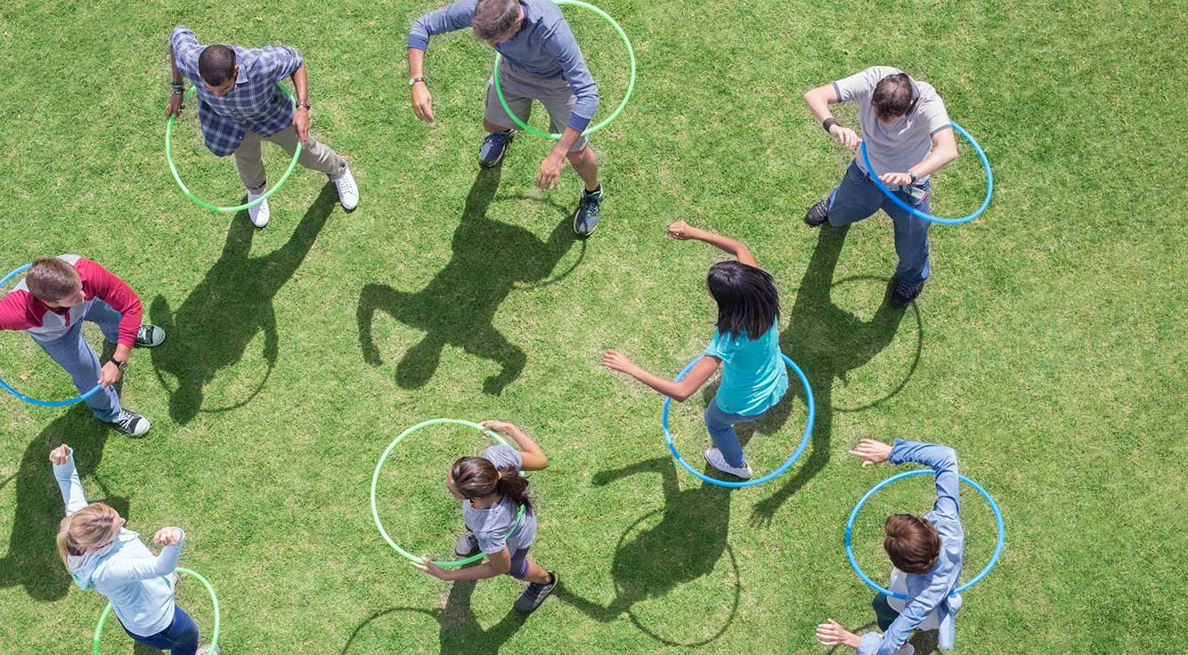 People hula hoop on a grassy field.