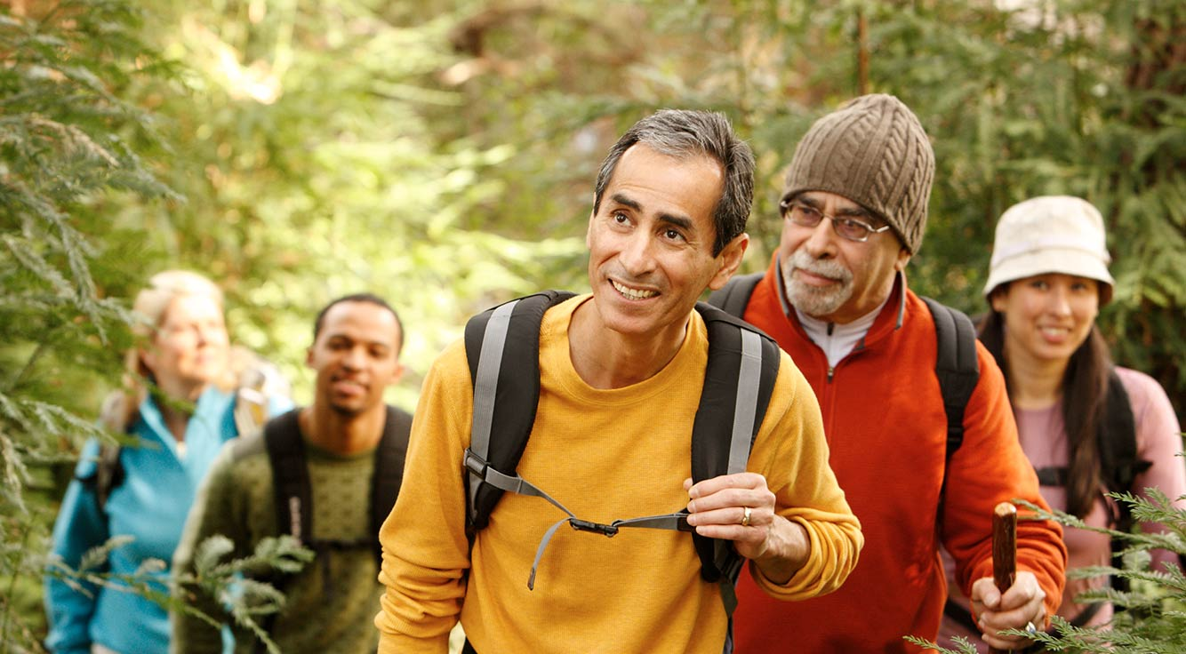Two older men lead a few other hikers through the woods.