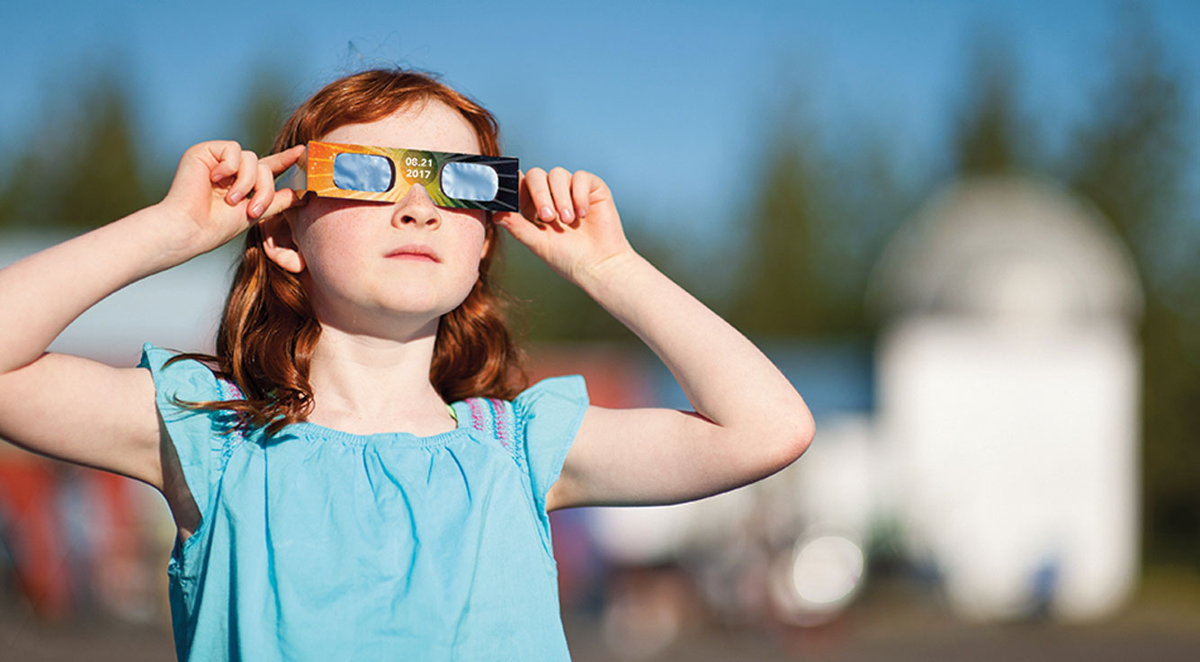 A little girl peers through specialized eclipse glasses.