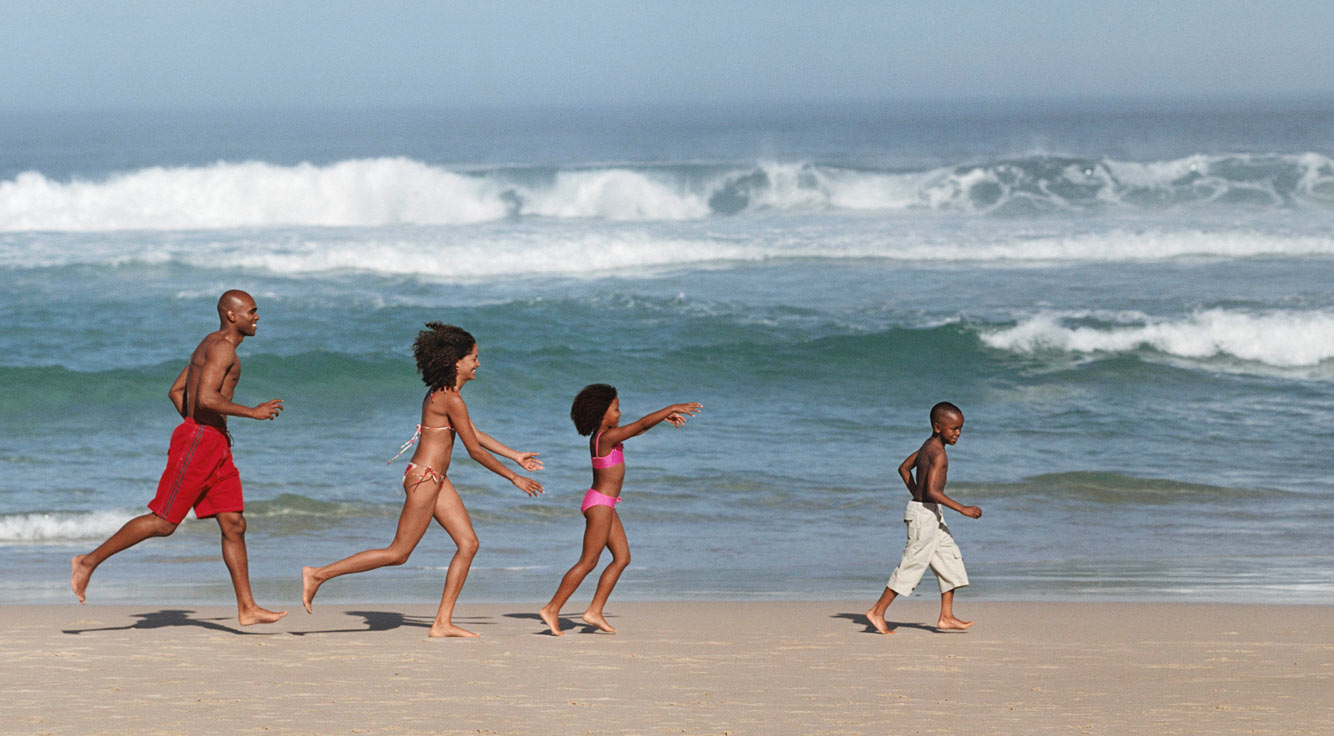 A man, a woman, and two children run along an ocean shore.