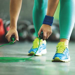 A person in sports gear picks up a jump rope.