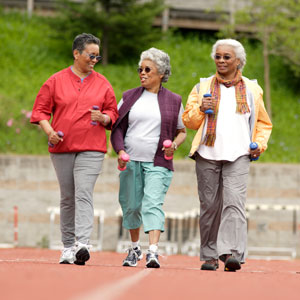 3 older woman walking outdoor track holding hand weights.