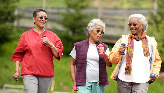 Three older woman walking on track while holding hand weights.