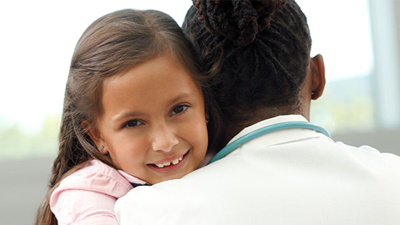 Young girl hugging medical professional.