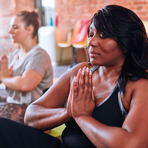 A woman meditates in a group exercise class.