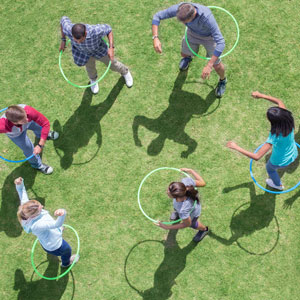 People play with hula hoops on a grassy lawn.