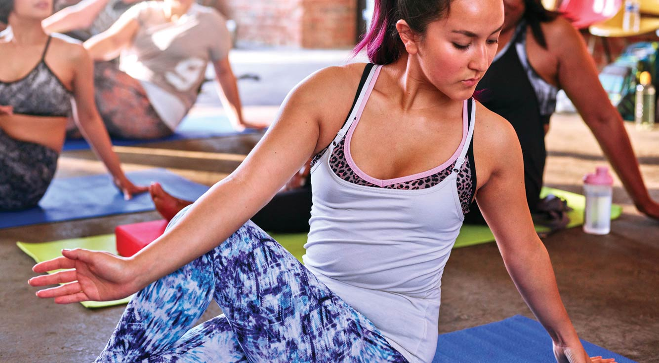 In a yoga class, a woman does a seated twist.