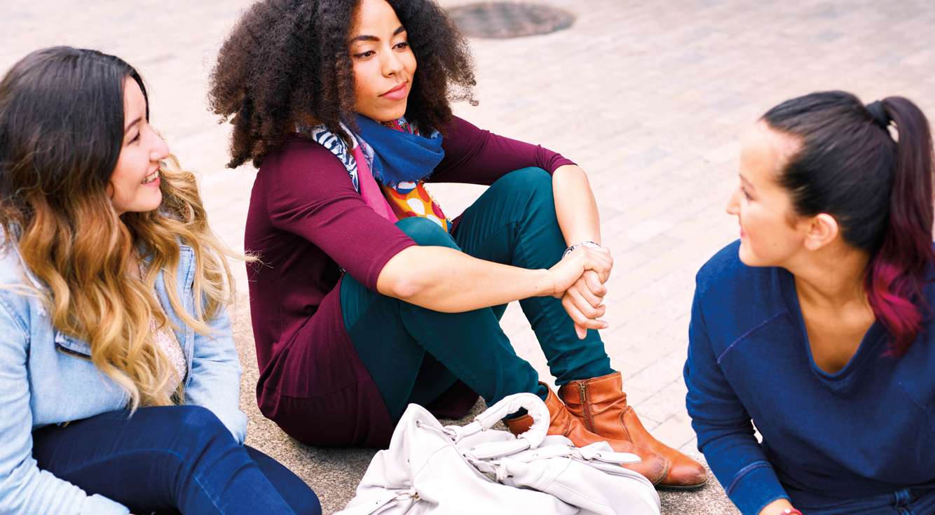 Three young women sit and talk.