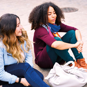 Three young women sit outside and chat.