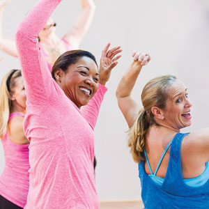 Beaming women dance in an exercise class.